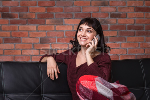 Happy beautiful young woman sitting and taking on mobile phone  Stock photo © deandrobot