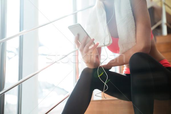 スポーツウーマン 座って スマートフォン イヤホン ジム クローズアップ ストックフォト © deandrobot
