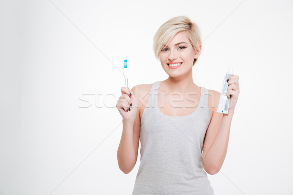Happy blonde woman holding toothbrush and toothpaste  Stock photo © deandrobot