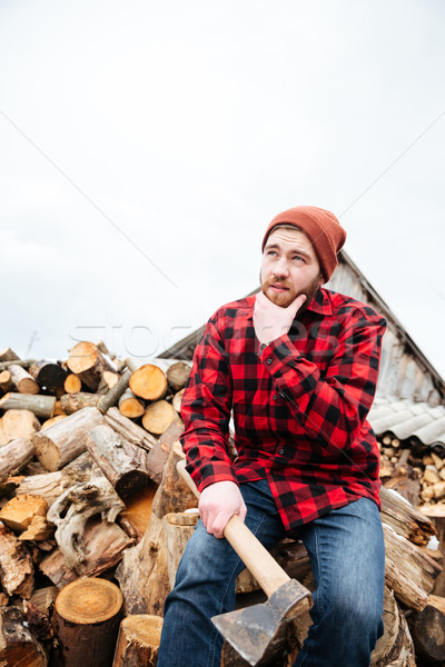 Pensive bearded man with axe sitting on logs and thinking  Stock photo © deandrobot