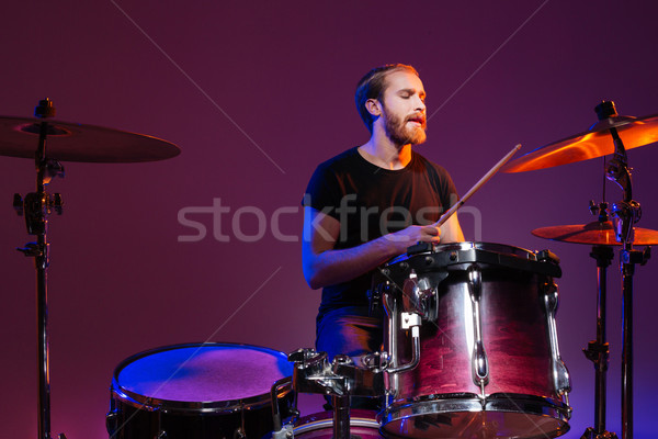Handsome man drummer sitting and playing on his kit  Stock photo © deandrobot