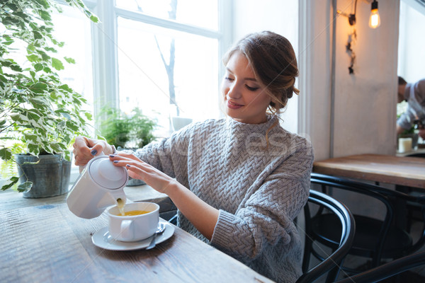 Woman drinking tea in cafe Stock photo © deandrobot