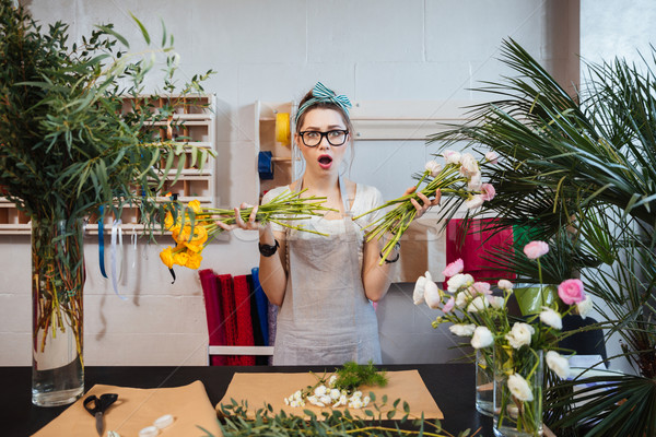 Amazed shoked woman florist holding two bunches of flowers Stock photo © deandrobot