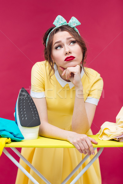 Thoughtful unhappy pinup girl ironing clothes Stock photo © deandrobot