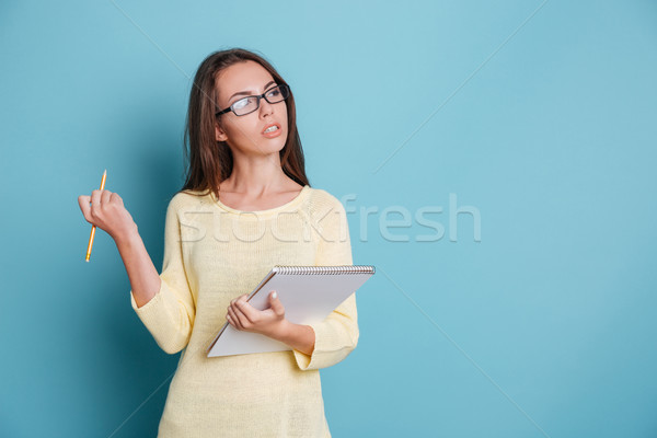 Young smart pensive girl thinking about something holding colorful binders Stock photo © deandrobot