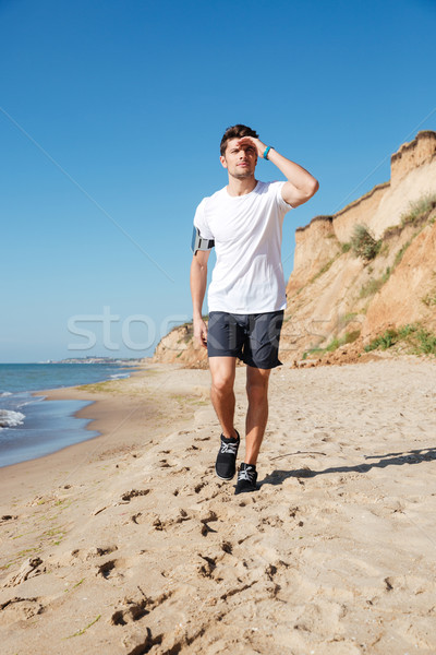 Sportsman walking along the beach Stock photo © deandrobot