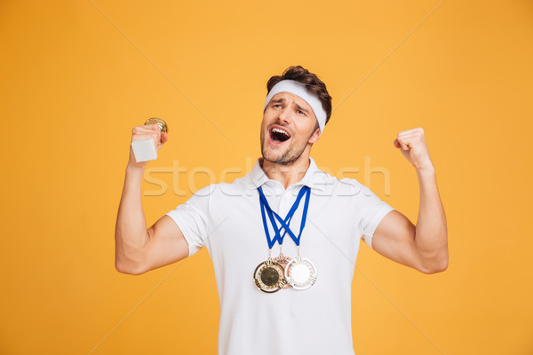 Successful sportsman with three medals shouting and celebrating victory Stock photo © deandrobot