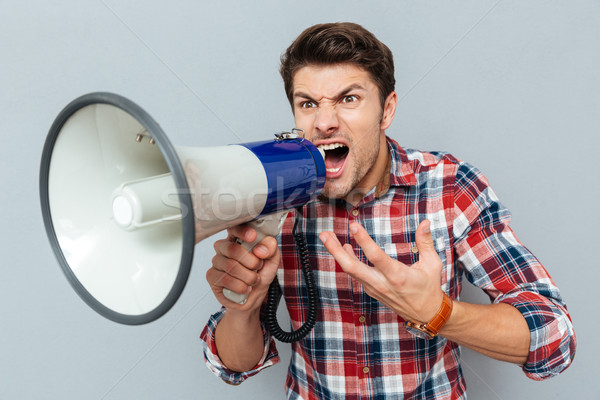 Retrato homem gritando megafone isolado cinza Foto stock © deandrobot