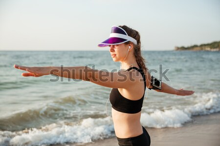 Runner girl wearing earphones and running armband ready for workout Stock photo © deandrobot