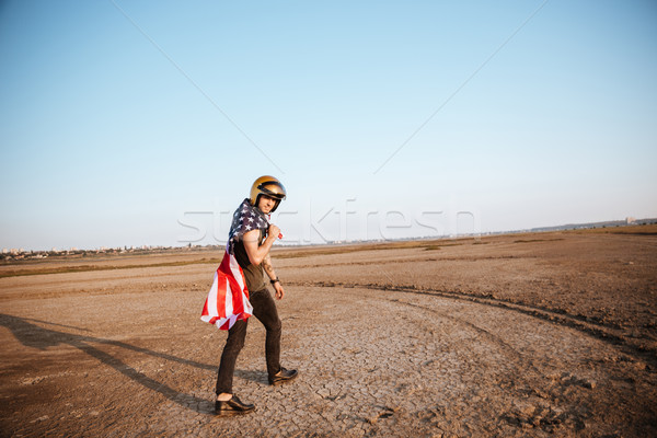 Man wearing american flag cape and golden helmet walking Stock photo © deandrobot