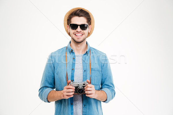 Smiling man in hat and sunglasses using old photo camera Stock photo © deandrobot