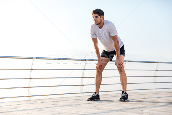Handsome tired young sportsman standing on pier Stock photo © deandrobot