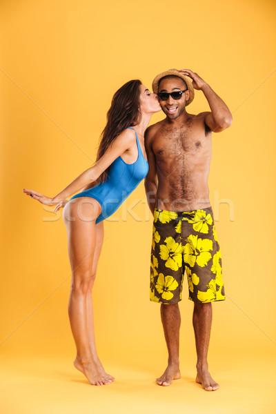 Pretty girl in swimsuit kissing her african boyfriend Stock photo © deandrobot