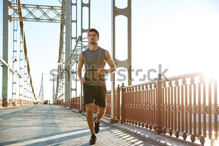 Sports man running along big modern bridge at sunset light Stock photo © deandrobot