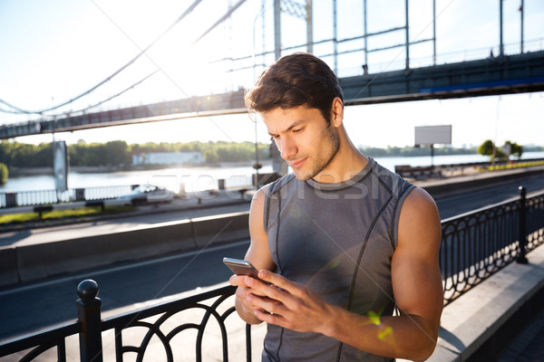 Runner using mobile smart phone and standing at the bridge Stock photo © deandrobot