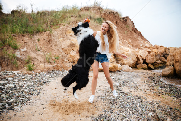 Joyful woman smiling and playing with dog on the beach Stock photo © deandrobot