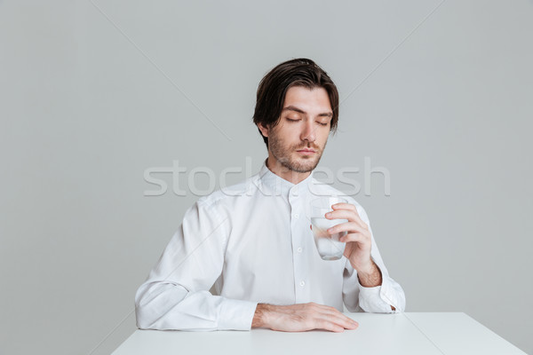 Man with eyes closed drinking from water glass at table Stock photo © deandrobot