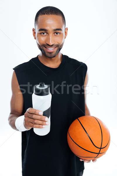 Young handsome sportsman holding basket ball and water bottle Stock photo © deandrobot