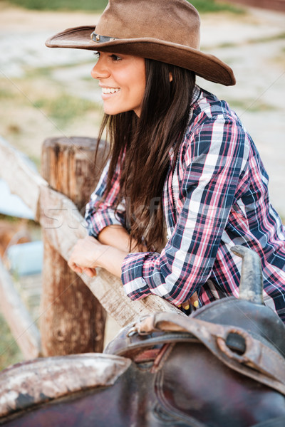 Close up portrait of a smiling cowgirl leaning on fence Stock photo © deandrobot
