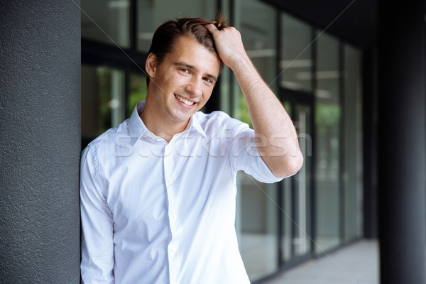 Cheerful confident young businessman standing and smiling Stock photo © deandrobot