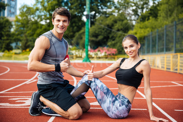 Young beautiful happy couple doing exercises at the stadium Stock photo © deandrobot
