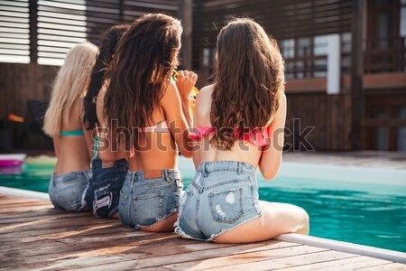 Cute young women sitting near swimming pool and drinking juice Stock photo © deandrobot