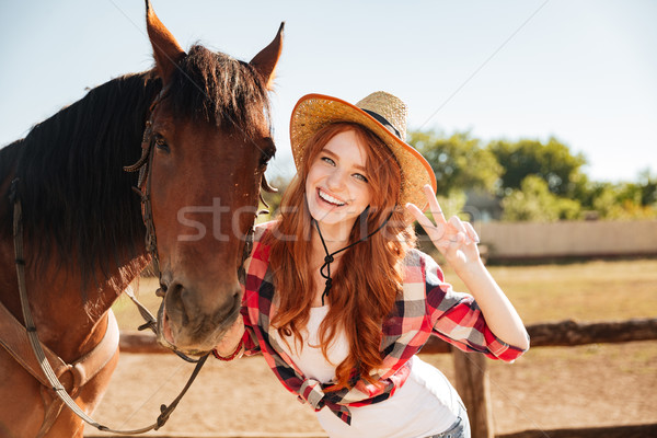 Happy woman cowgirl standing with horse and showing peace sign Stock photo © deandrobot