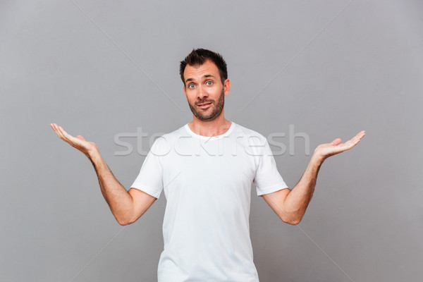 Young casual man standing and holding copyspace on both palms Stock photo © deandrobot