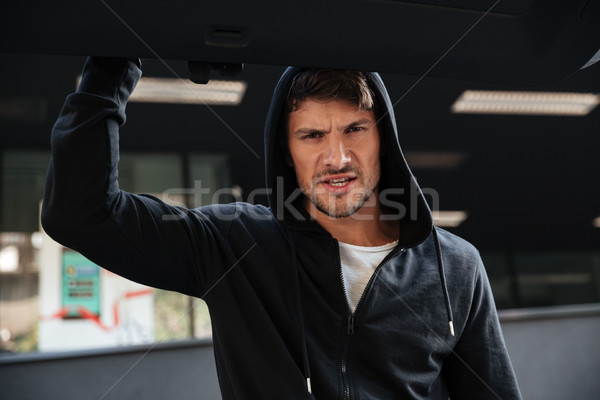 Angry criminal man closing car trunk outdoors Stock photo © deandrobot
