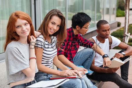 Wesoły młodych ludzi posiedzenia odkryty wraz Zdjęcia stock © deandrobot