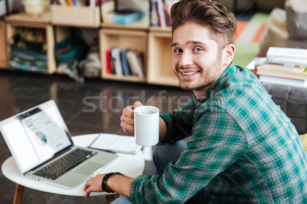 Side view of man on sofa by the table Stock photo © deandrobot