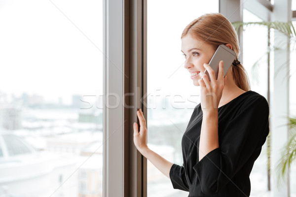 Side view picture of young lady worker talking by phone. Stock photo © deandrobot