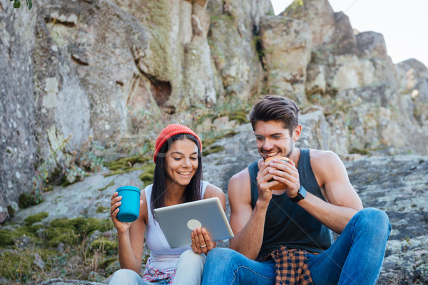 Couple having a break from hiking and using tablet computer Stock photo © deandrobot