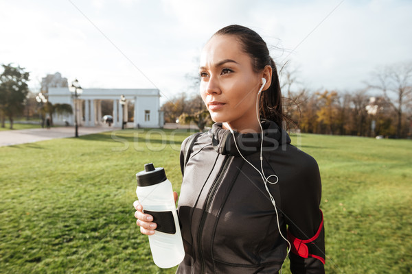 Beautiful runner in warm clothes looking aside in autumn park Stock photo © deandrobot