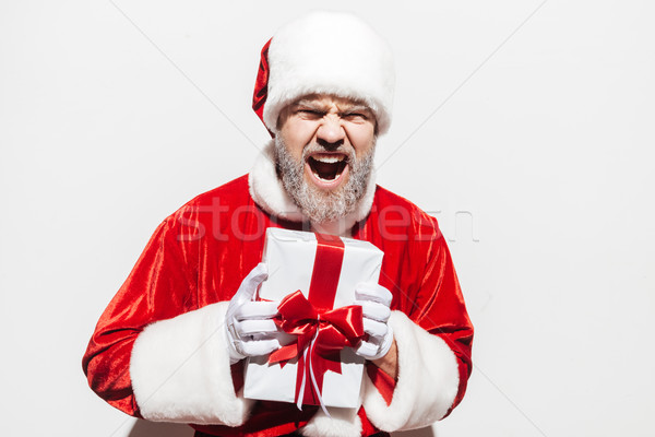 Mad irritated man santa claus holding present box and shouting Stock photo © deandrobot