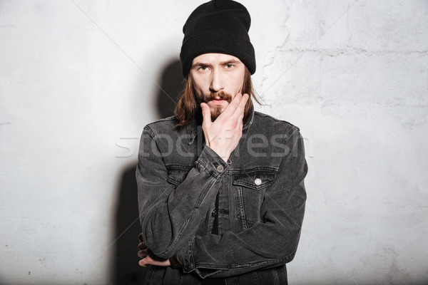 Young handsome hipster with beard and mustache looking at camera Stock photo © deandrobot