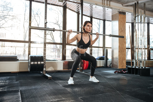 Fitness woman doing squats exercises in gym Stock photo © deandrobot