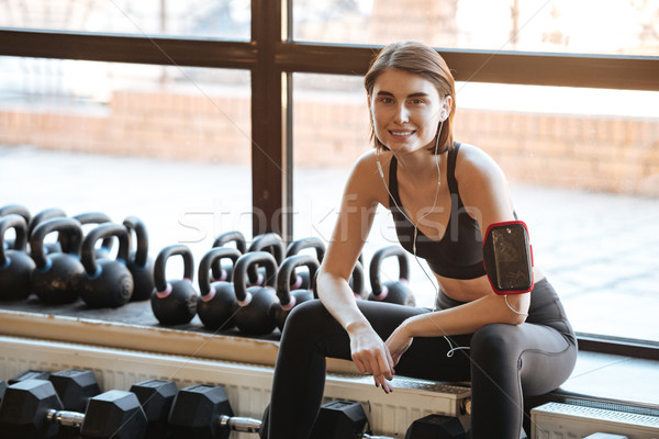 Happy woman athlete with earphones listening to music in gym Stock photo © deandrobot
