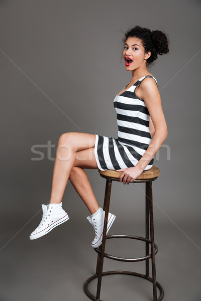 Portrait of a pretty afro american woman sitting on chair Stock photo © deandrobot