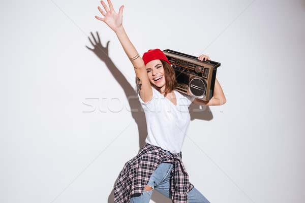 Young cheerful woman holding tape recorder. Stock photo © deandrobot