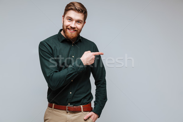 Smiling Bearded man in shirt pointing away Stock photo © deandrobot