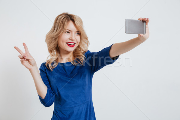 Young lady make selfie with peace gesture by phone Stock photo © deandrobot