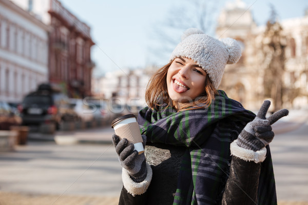 Woman with cup of coffee winking and showing tongue outdoors Stock photo © deandrobot