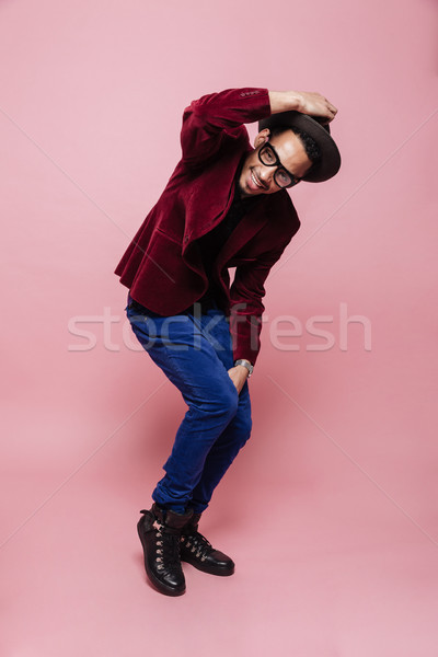 Smiling african man in eyeglasses wearing jacket and posing Stock photo © deandrobot