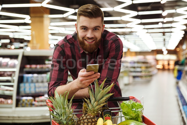 Cheerful man in supermarket with shopping trolley Stock photo © deandrobot