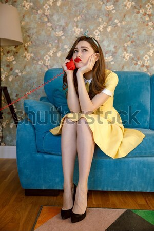 Tired young pin-up lady talking by phone. Stock photo © deandrobot