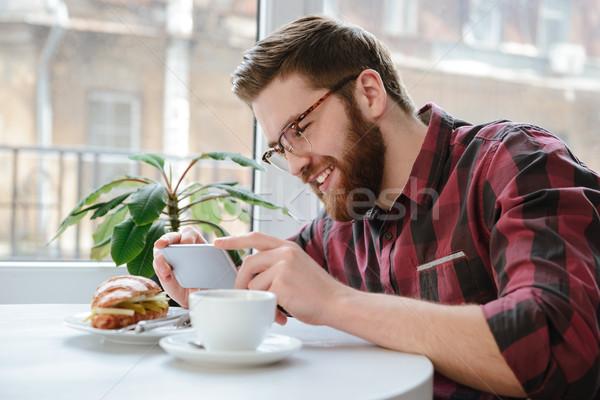 Sorridere uomo smartphone pranzo cafe Foto d'archivio © deandrobot