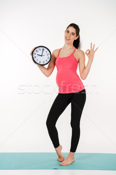 Full length portrait of a happy young pregnant woman Stock photo © deandrobot
