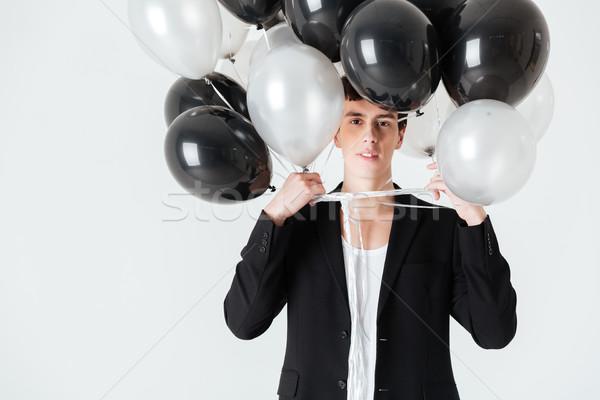 Smiling man holding air balloons Stock photo © deandrobot