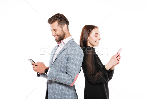 Cheerful young loving couple chatting by phones. Stock photo © deandrobot